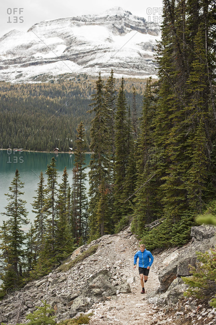 Athletic young man runs on a mountain trail beside a lake
