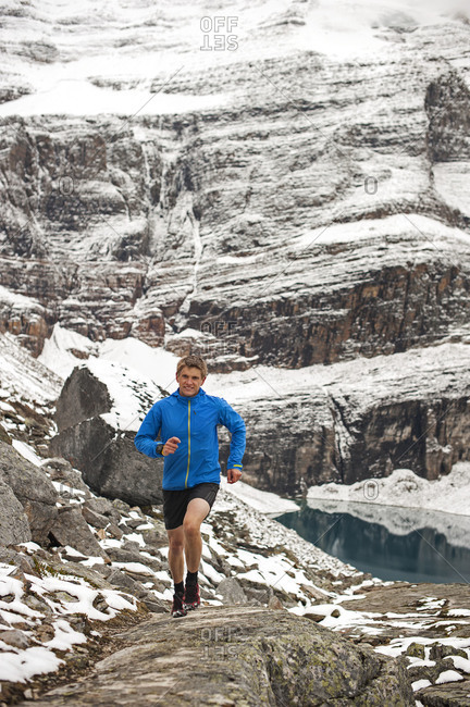 Athletic young man running happily along winter mountain trail