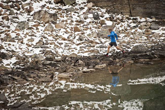Athletic young man runs on a snowy mountain trail beside a lake with his reflection