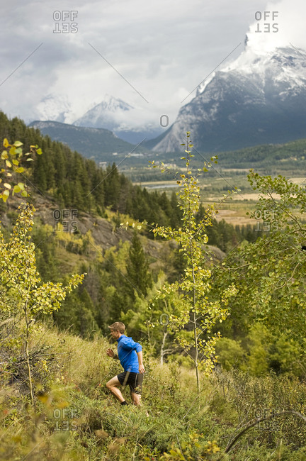 Man running up a lush fall trail