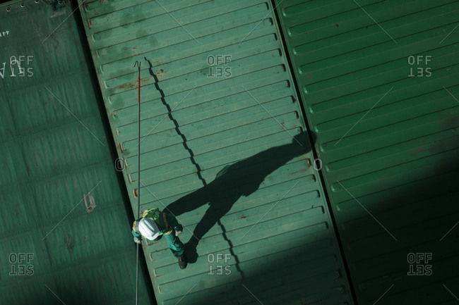 A top view of a man unlocking cargo containers at the dock of Khorfakhan port, Sharjah, UAE