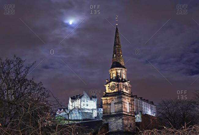 Spire of St Cuthbert\'s Church and Edinburgh Castle at night with full moon, Edinburgh, Scotland
