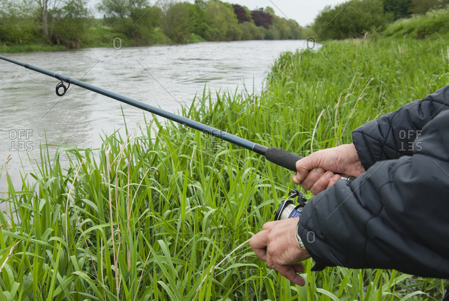 Close-up of man fishing at river Nore, Thomastown, County Kilkenny, Leinster, Republic of Ireland