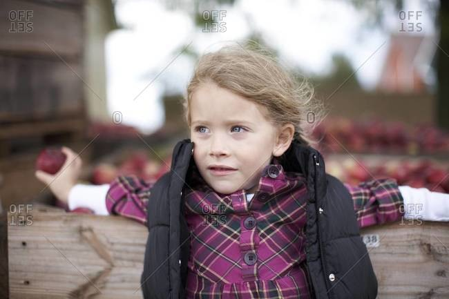 Girl leaning on apple crate