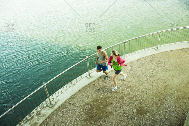 Young couple running by Water, Worms, Rhineland-Palatinate, Germany