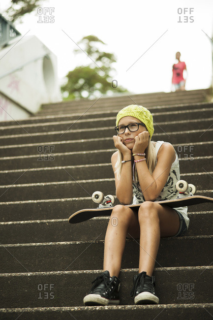 Girl Sitting on steps with skateboard, Mannheim, Baden-Wurttemberg, Germany