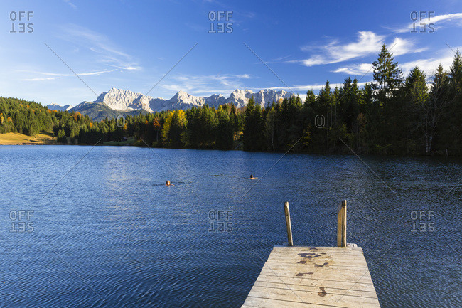 Wooden dock at wagenbruchsee with Karwendel Mountains in Autumn, Bavaria, Germany