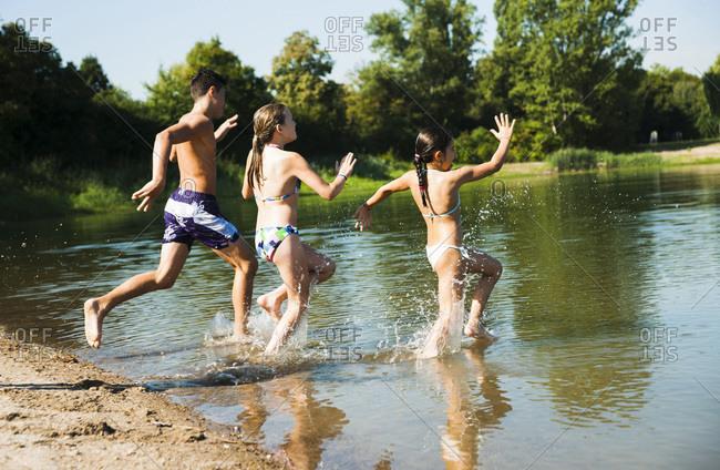 Kids running into lake, Lampertheim, Hesse, Germany