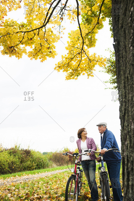 Elderly couple standing by tree with Bicycles, Mannheim, Baden-Wurttmeberg, Germany