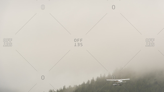 Float plane flying in foggy weather at the Queen Charlotte Islands, Canada