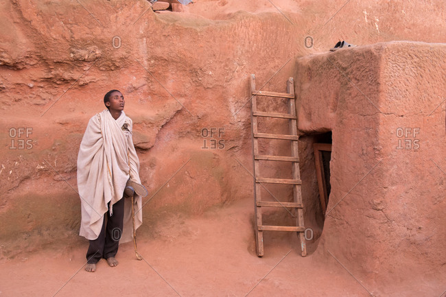 Lalibela, Ethiopia - January 5, 2014: Ethiopian man standing by the wall of a rock-hewn church in Lalibela, Ethiopia