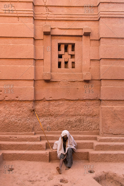 Lalibela, Ethiopia - January 5, 2014: Ethiopian man sitting by the wall of a rock-hewn church in Lalibela, Ethiopia