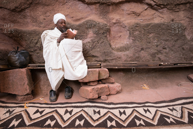Lalibela, Ethiopia - January 5, 2014: Pilgrim reading bible in Lalibela, Ethiopia beside centuries-old churches hewn from the rock