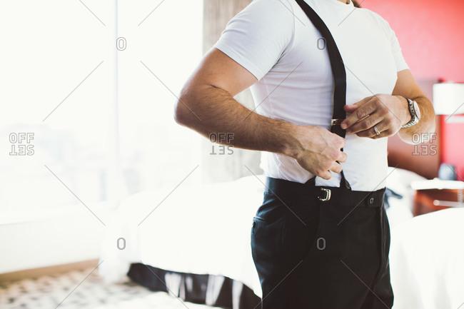 Man adjusting suspenders