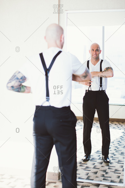Man adjusting suspenders in front of mirror