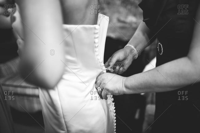 Woman zipping bride's wedding dress