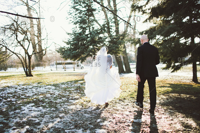 Rear view of bride and groom walking outside
