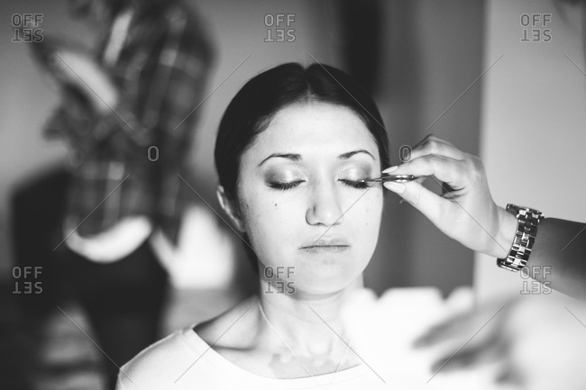 Make up artist applying fake eyelashes to bride