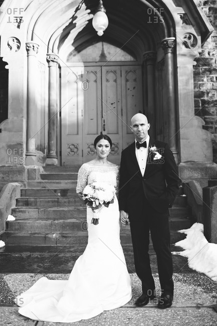 Newlyweds standing in front of a church