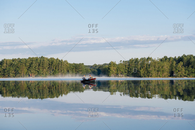 Two friends fish on a lake on a summer morning