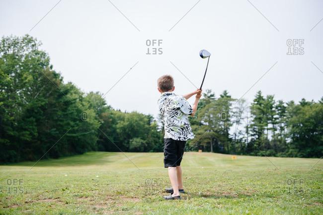 Kid swinging a golf club