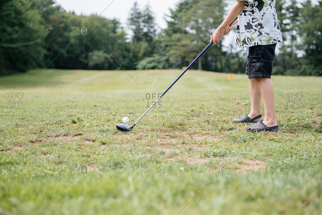 Boy preparing to hit golf ball