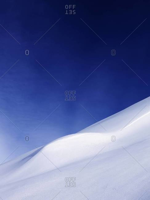 Abstract image of a snow-covered mountain under a blue sky