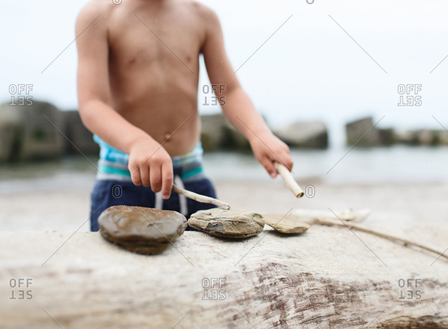 Child plays with rocks on beach