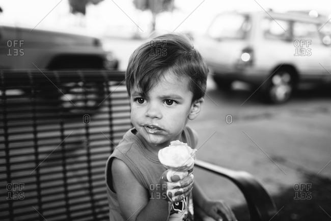 Child eats ice cream on street bench