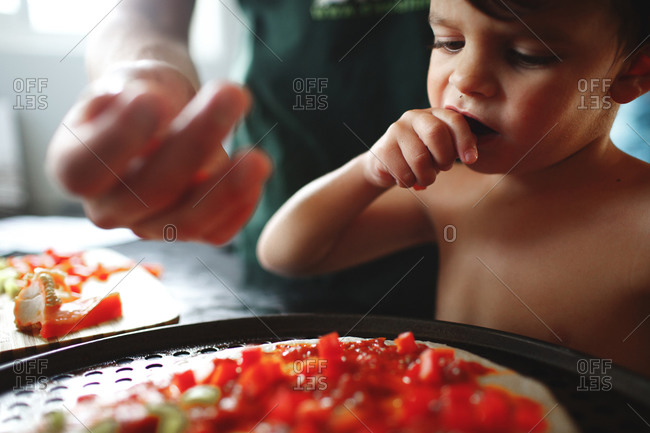 Child yawns while making pizza