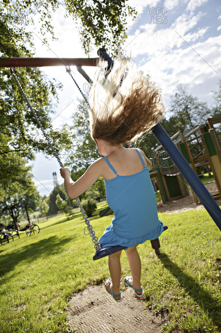Young girl swinging in the park
