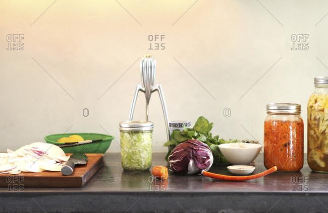 Pickled vegetables in jars arranged on table