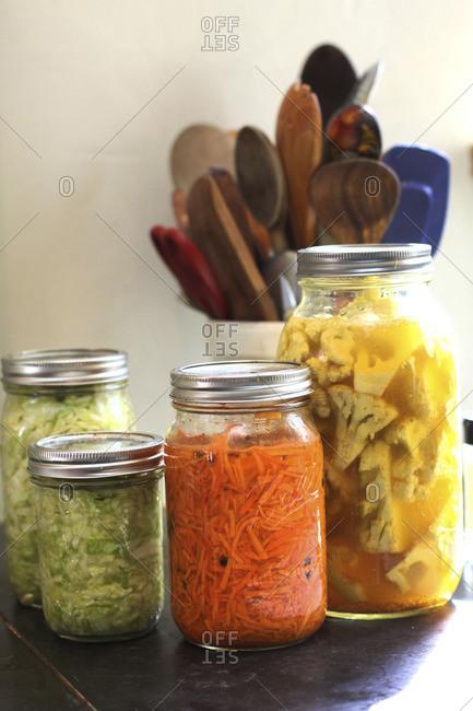 Pickled vegetables in jars displayed on table