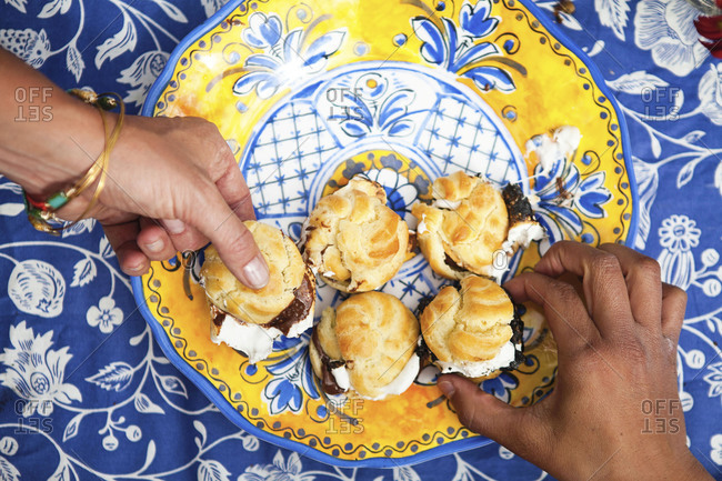 Hands picking profiteroles from the plate