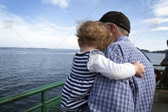 Elderly man holding his granddaughter on ferry's deck