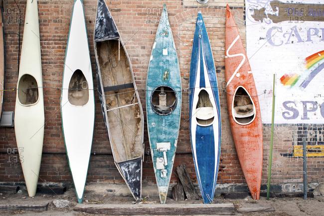 Kayaks leaning against brown brick wall