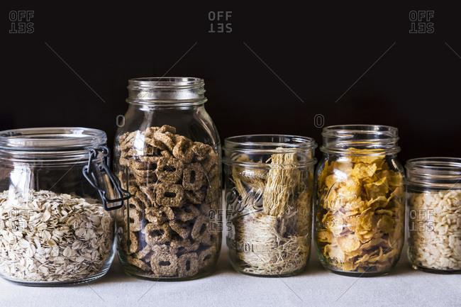 Studio shot of various cereal in glass jars