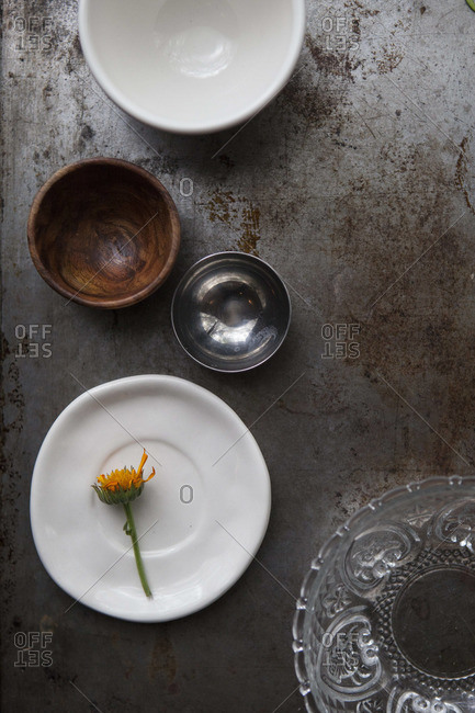Bowls and a flowers on a tarnished metal surface