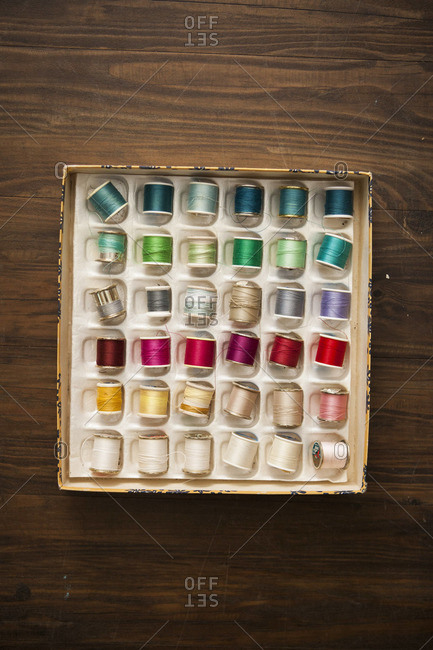 A vintage box of colorful thread on a wood floor