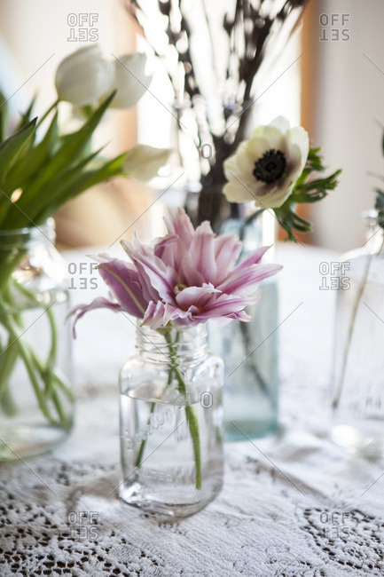 A collection of flowers on a lace tablecloth