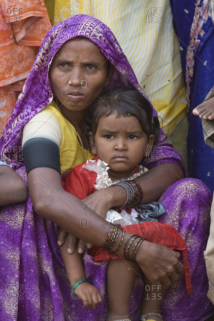 July 24, 2005: Mother and her child listen at a squatter village outside of Hyderabad, India