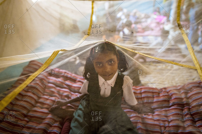 April 11, 2012: Girl sitting under mosquito net at an orphanage in India