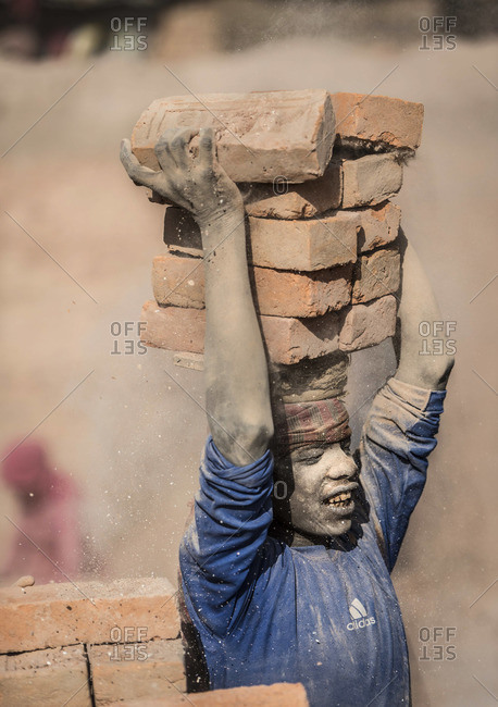 March 24, 2013: Young boy holding bricks on his head at a brick factory in Nepal
