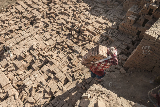 Young boy carries bricks on his head at a brick factory in Nepal