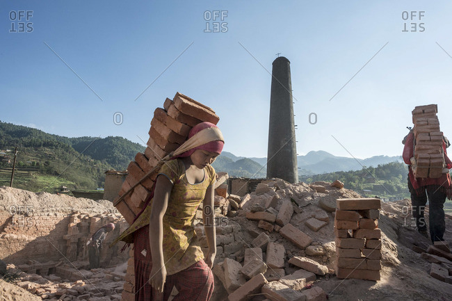 March 24, 2013: Girl carries a heavy load of bricks at a brick factory in Nepal