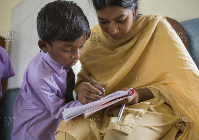 Female teacher helps one the youngest students with his lesson, in Pakistan