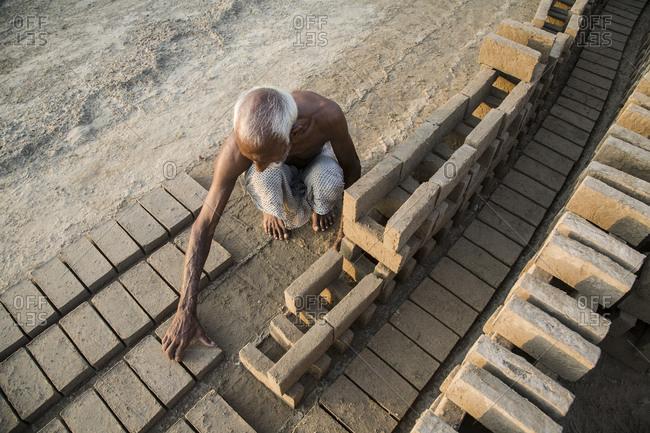Male Pakistani worker arranging bricks at a brick factory