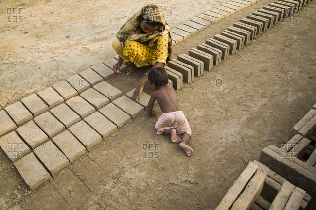 Pakistani woman tends to her child while working at brick factory