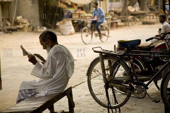 Pakistani man reads newspaper on street