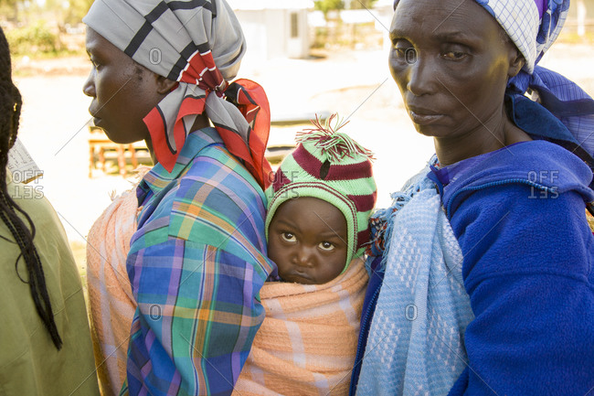 Women and child wait in a line for medical aid in Kenya